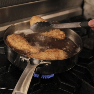 Chicken thighs being placed in frying pan