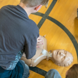 Child practicing CPR during school training