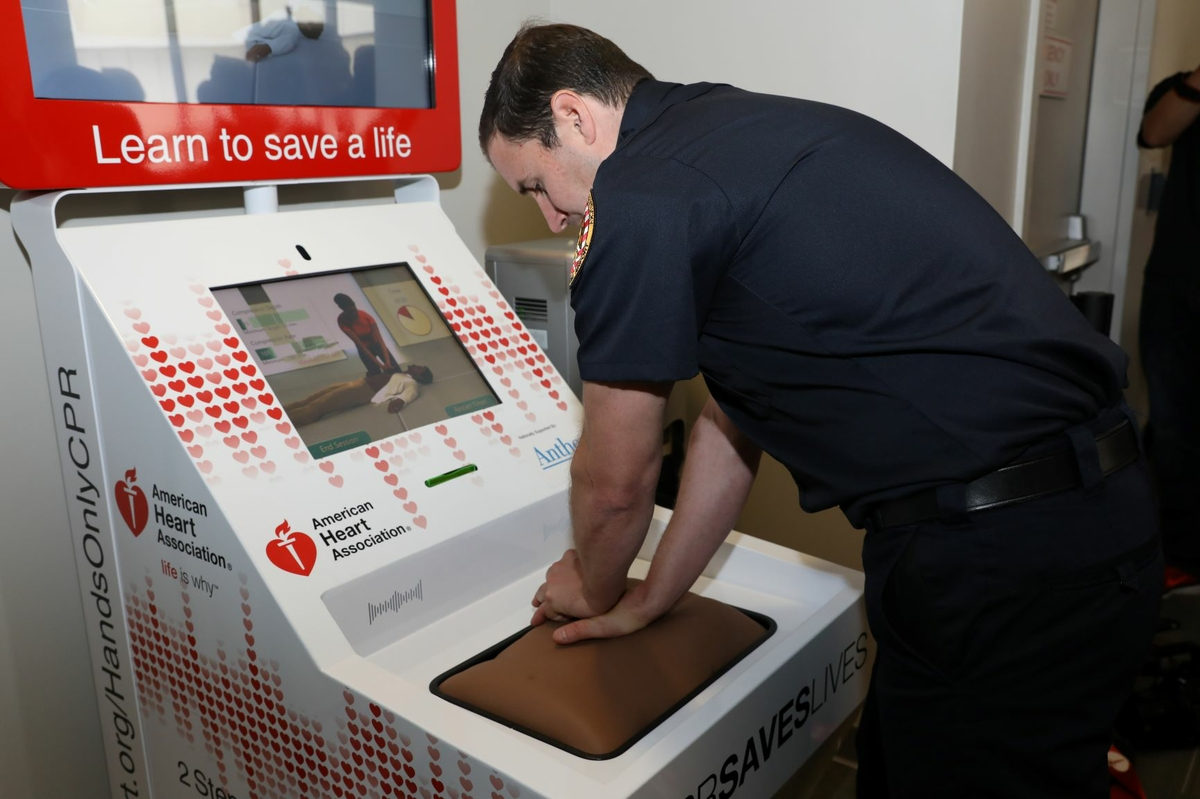 Man practices Hands-Only CPR on kiosk