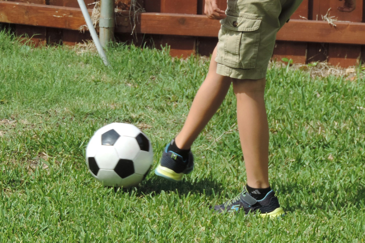 Boy kicks soccer ball