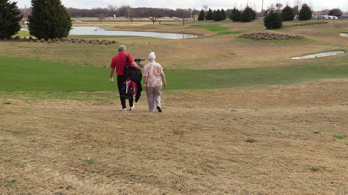 Man and woman walking on golf course