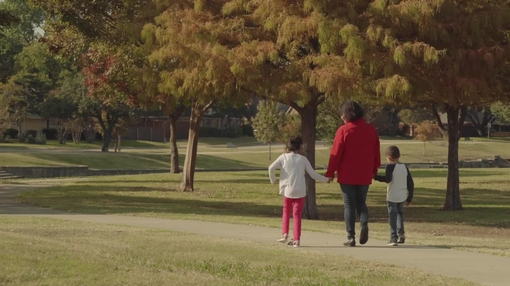 Woman walking with grandchildren at park