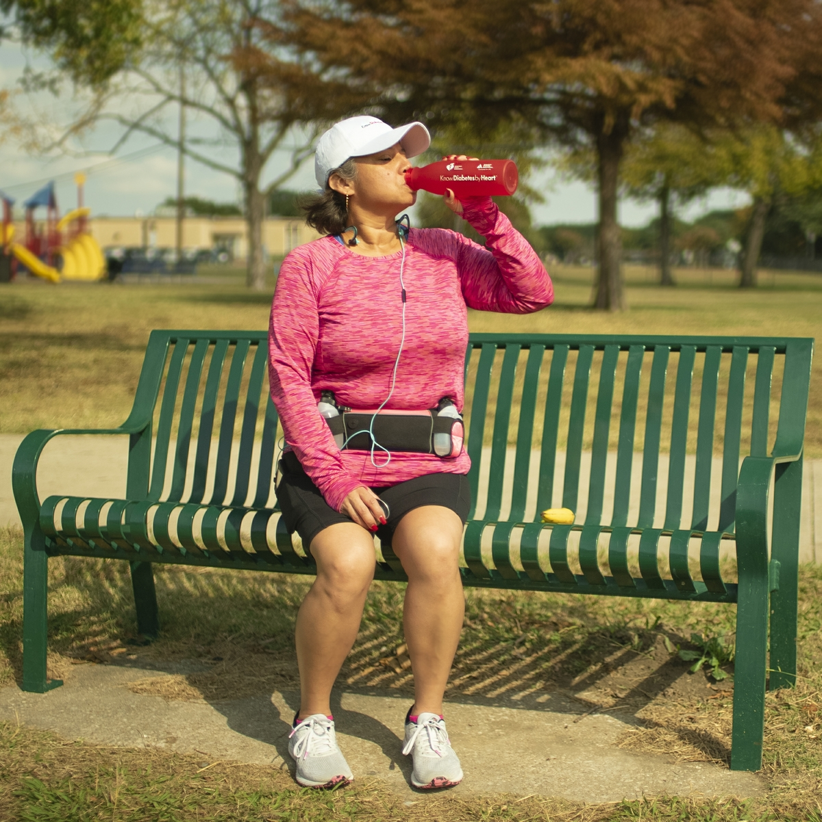 Woman drinking water on park bench