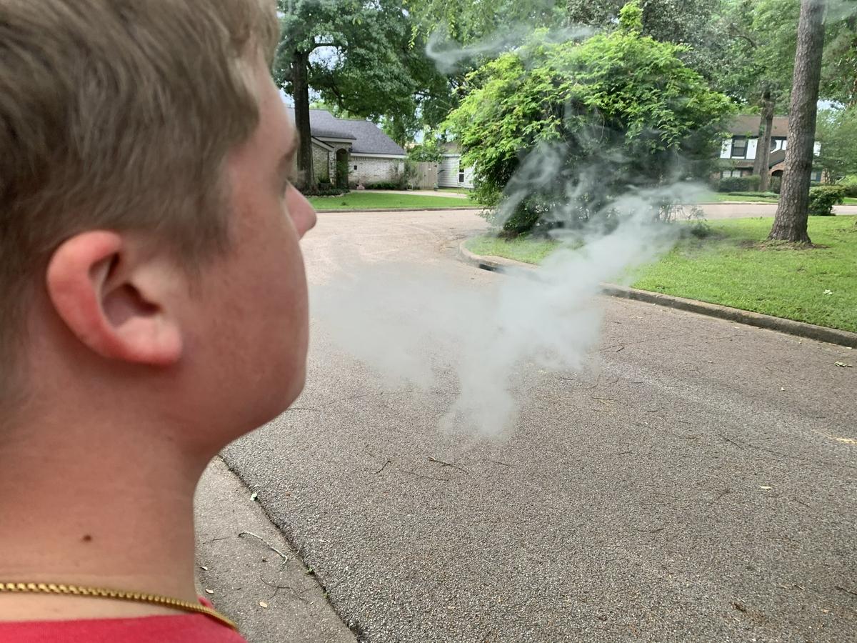 Teen blowing e-cigarette smoke - vaping