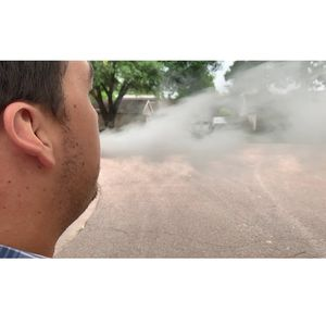 Man blowing e-cigarette smoke - vaping