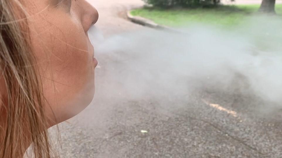 Woman blowing e-cigarette smoke - vaping