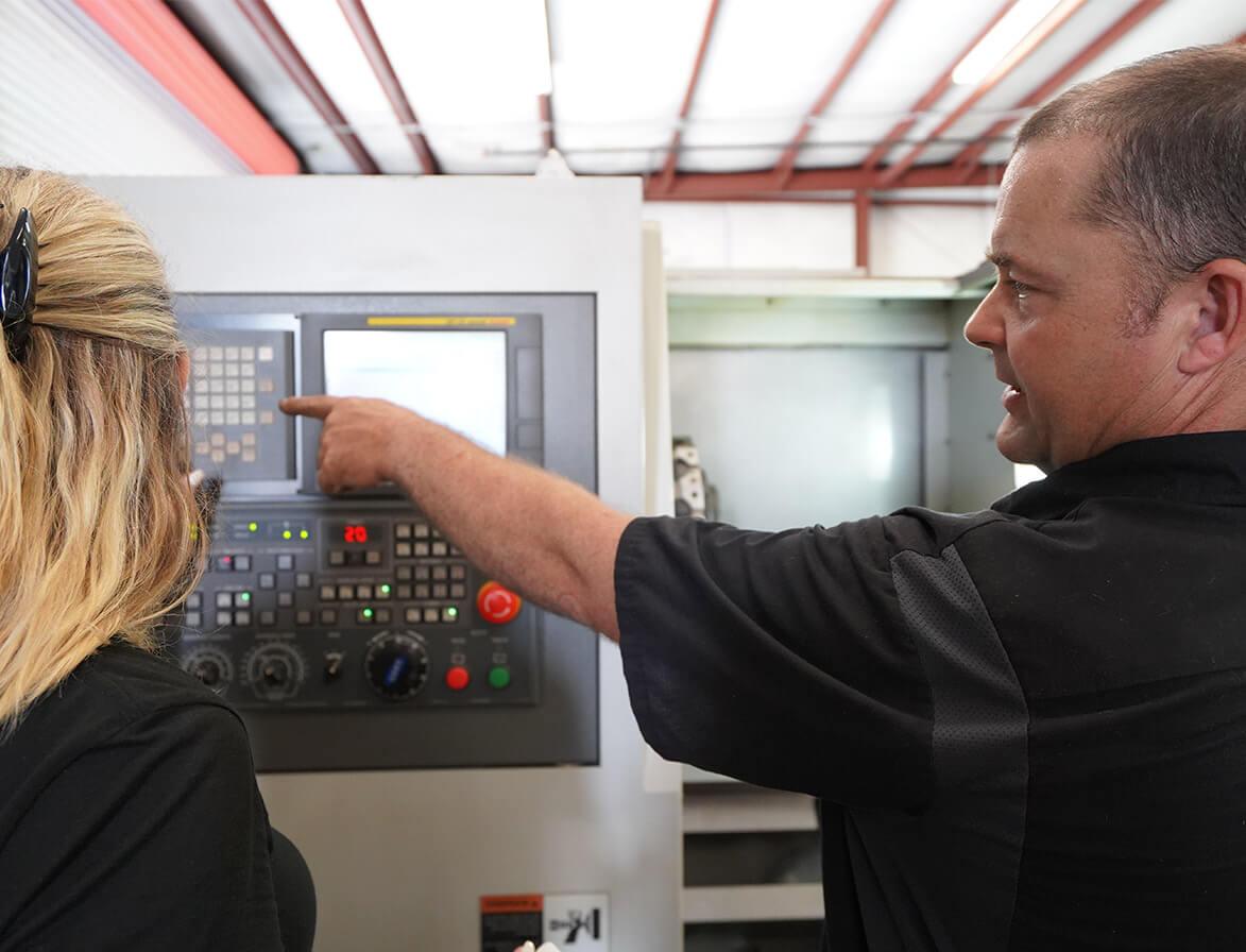 a guy showing a woman a CNC machine