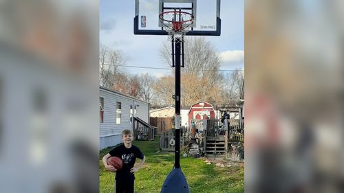 Image for A FedEx driver surprised a boy with a new basketball and hoop after she noticed him playing with a broken one