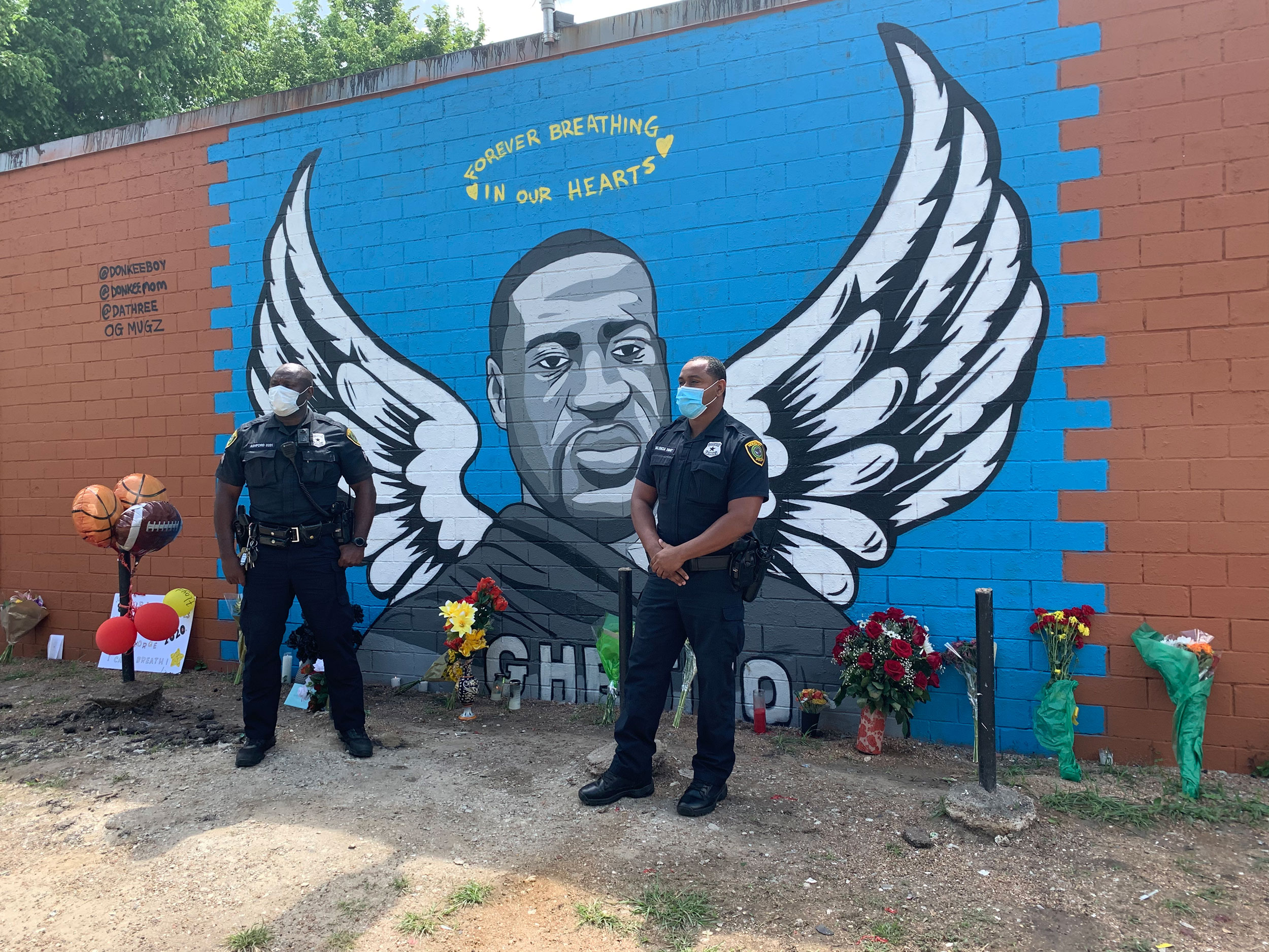Houston police officers pay their respects to George Floyd at a mural in his hometown