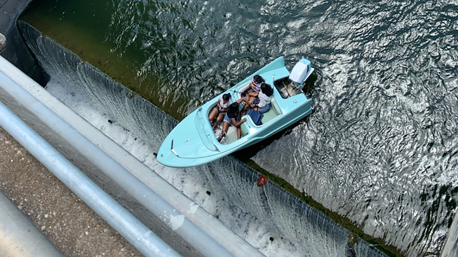 Four people were rescued off a boat 'teetering' at the edge of a Texas dam, police say