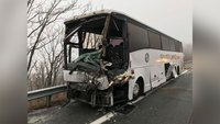 A bus crashes into a semi truck, splitting it in half and leaving 19 people hospitalized