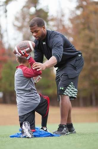 Coach Quincy working with a young football player.