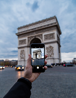 a photograph of an iPhone taking a photograph of le Arc de Triomphe