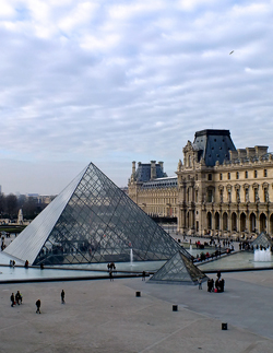 le Louvre with another large building behind and to the right on a partly cloudy day