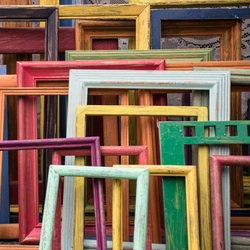 frames of many colors and sizes leaning against the wall