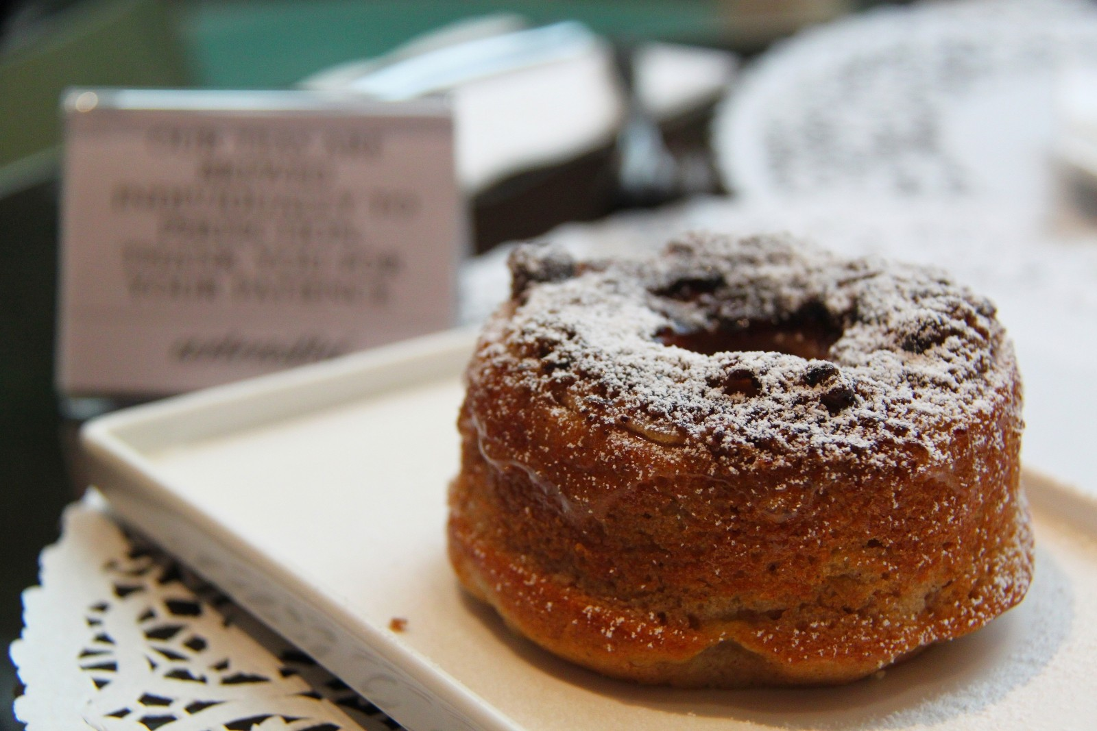 a close shot of an old-fashioned donut with powdered sugar on top