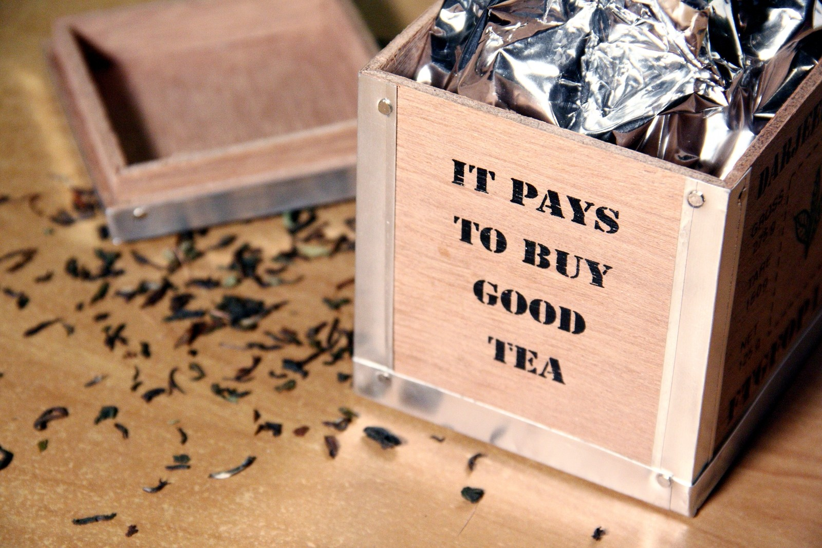 'It pays to buy good tea' printed on the side of an open box of tea