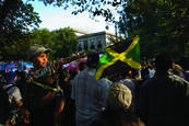 Young Boy Pointing Jamaican Flag by Scott Brock