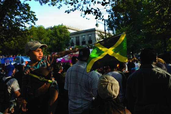 Young boy pointing jamaican flag
