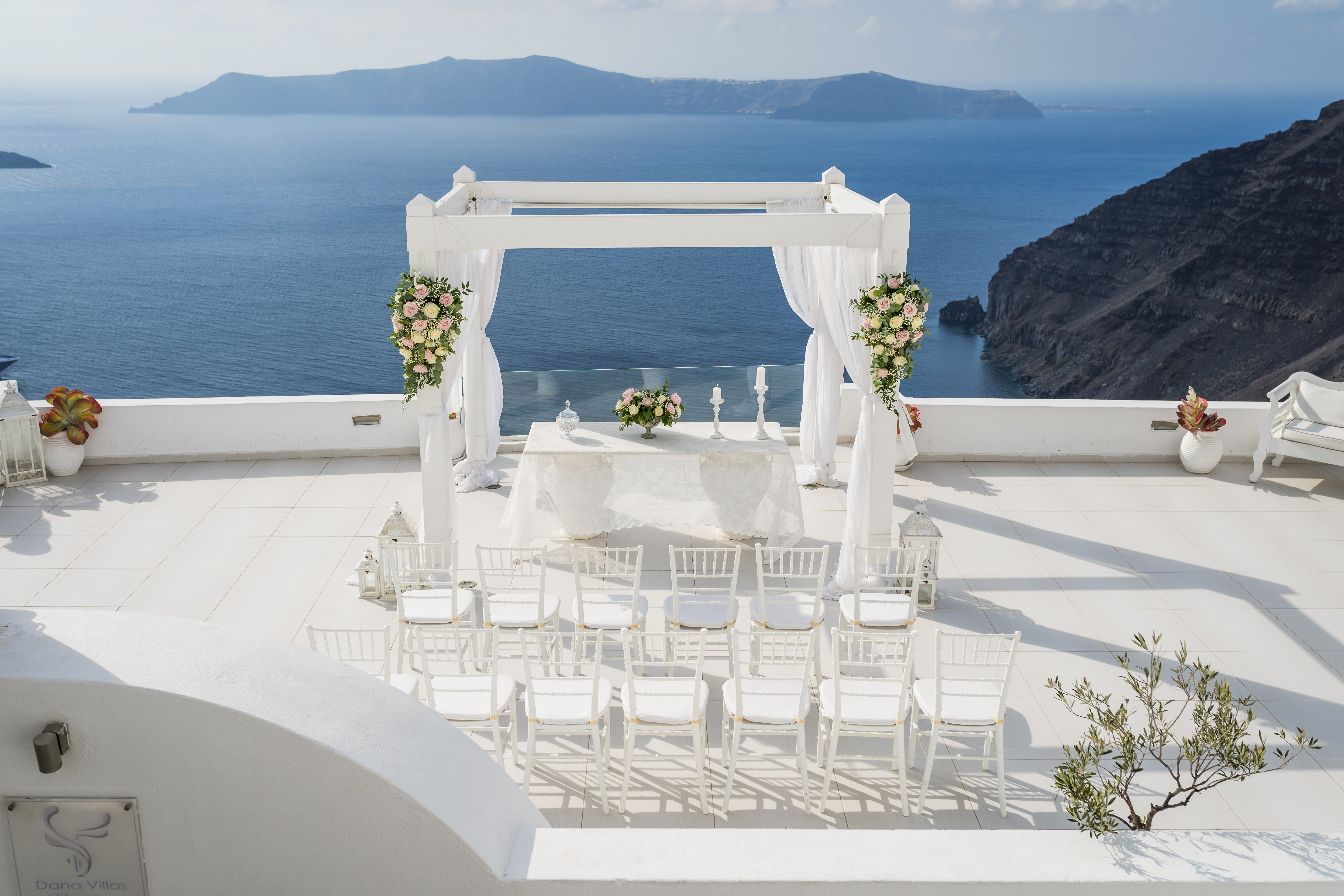 all white waterfront wedding ceremony setup in Santorini, Greece