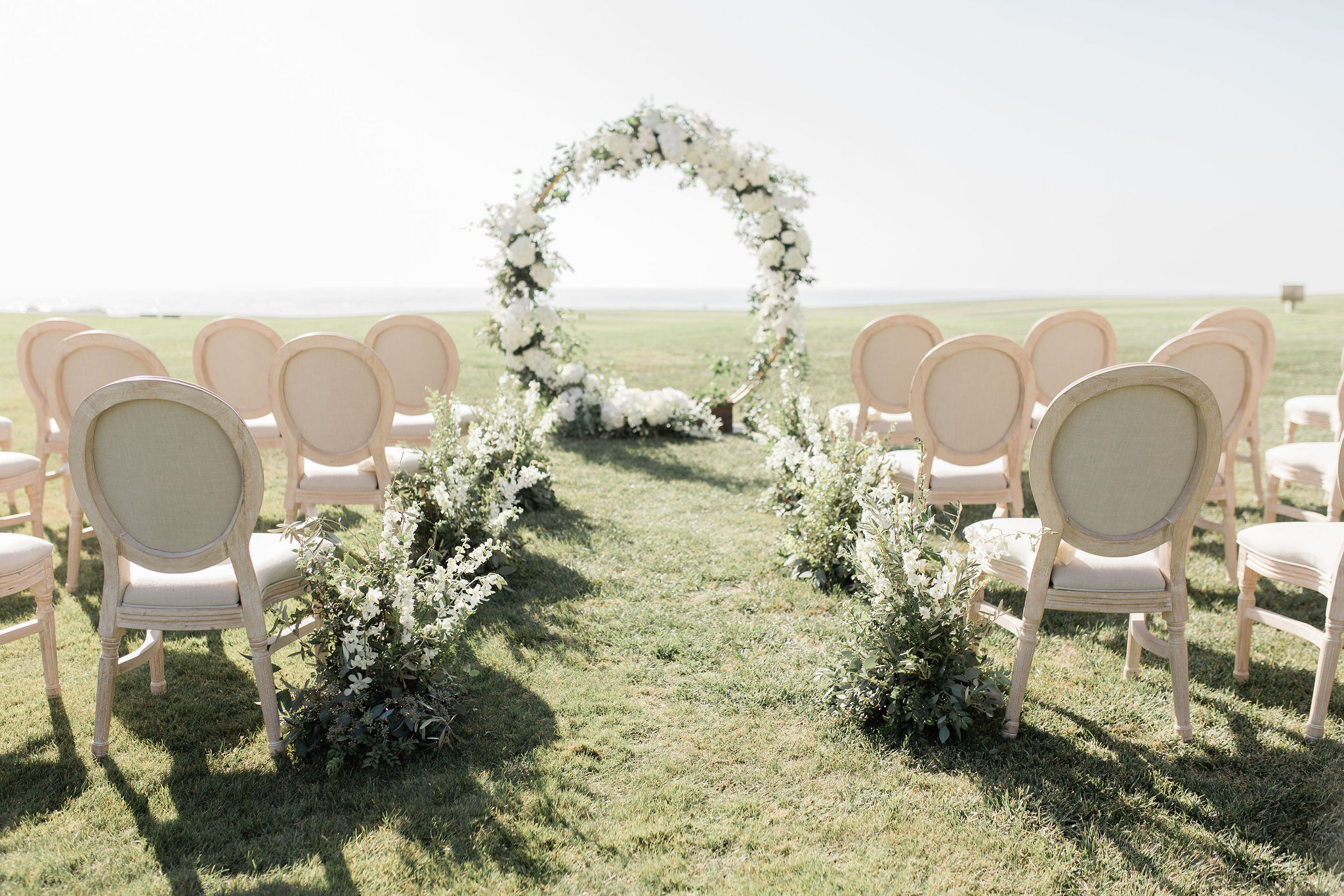 circular floral arch and chair setup outdoors for wedding ceremony
