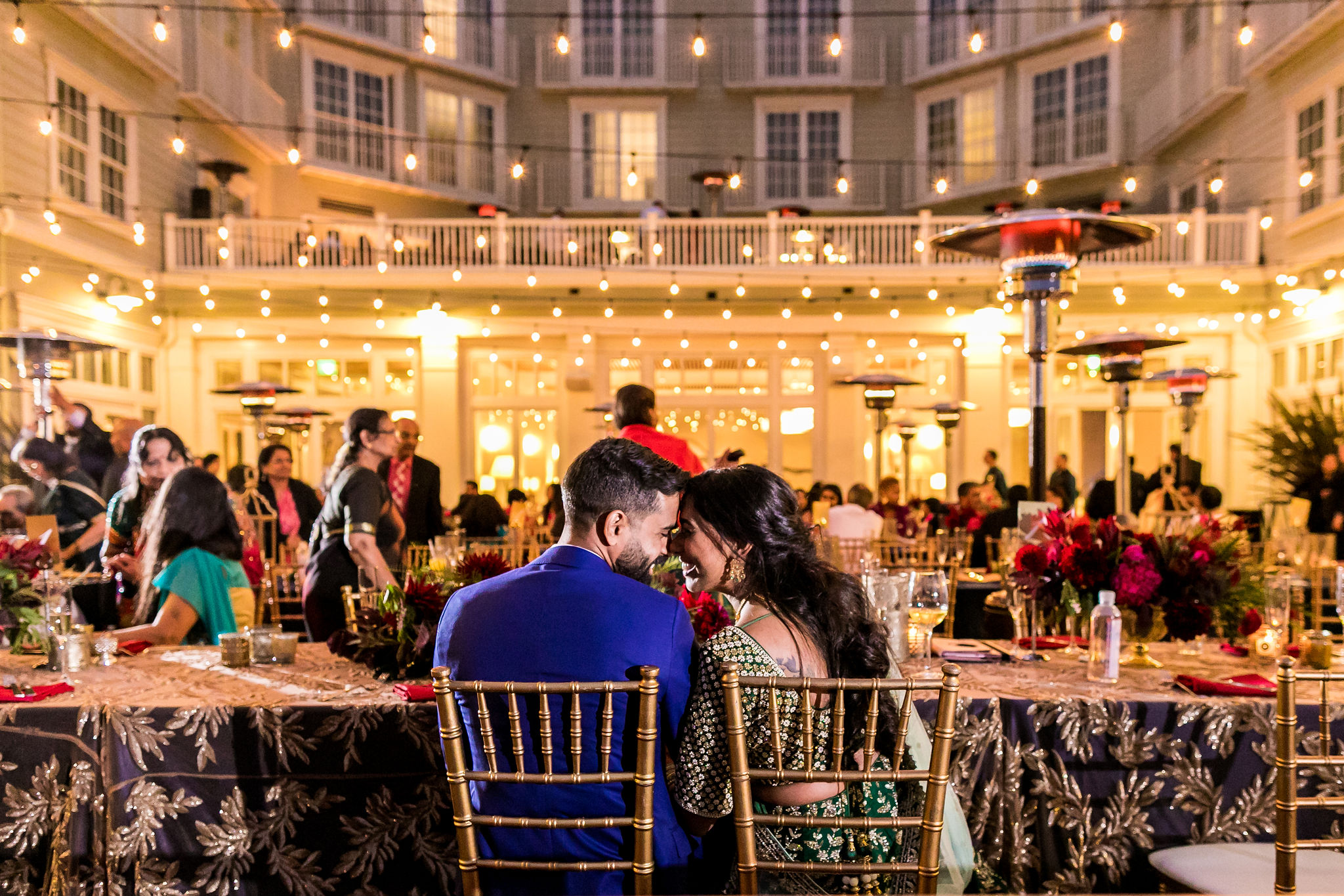 couple at sweetheart table snuggled in front of wedding party at full indoor reception with bright lights