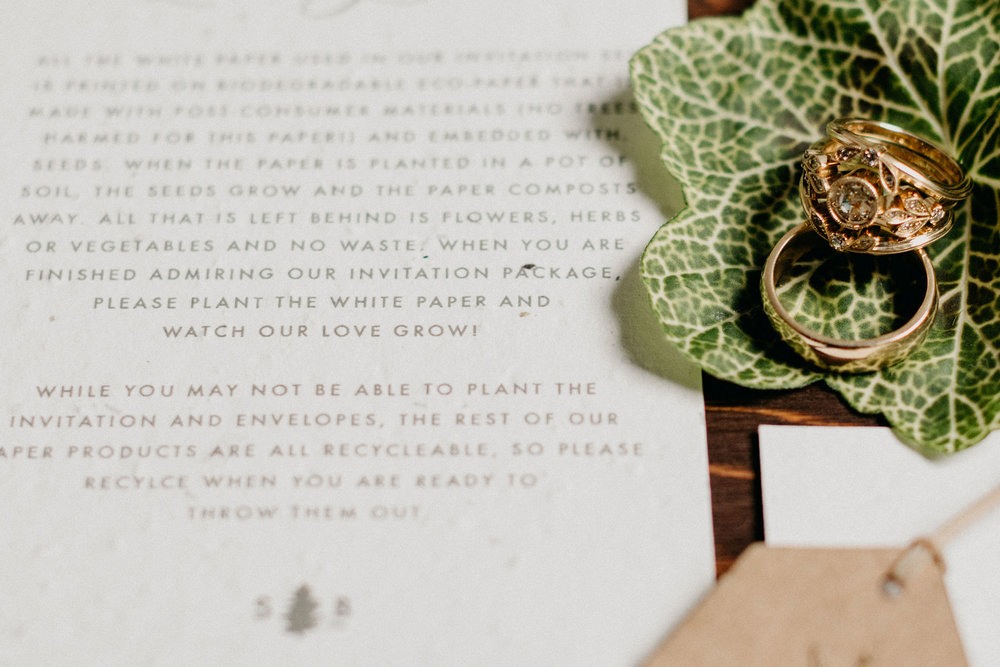 letter with leaf holding gold wedding rings