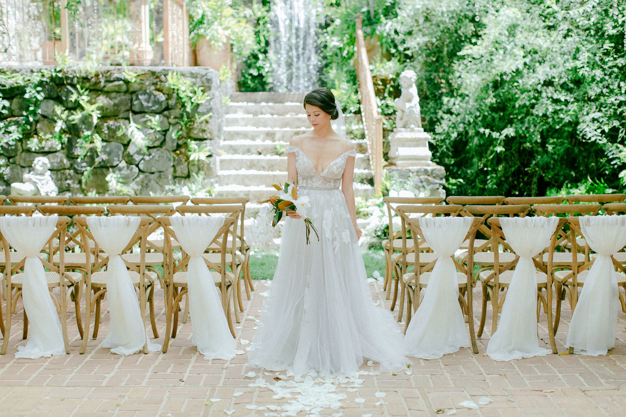 bride standing with bouquet, surrounded by gold chairs in front of waterfall
