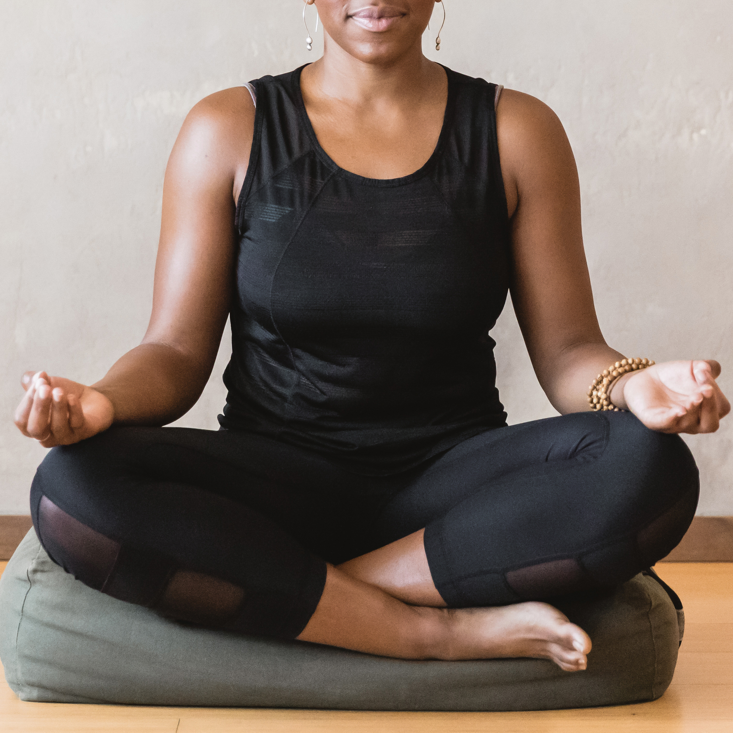 woman wearing black workout clothes meditating