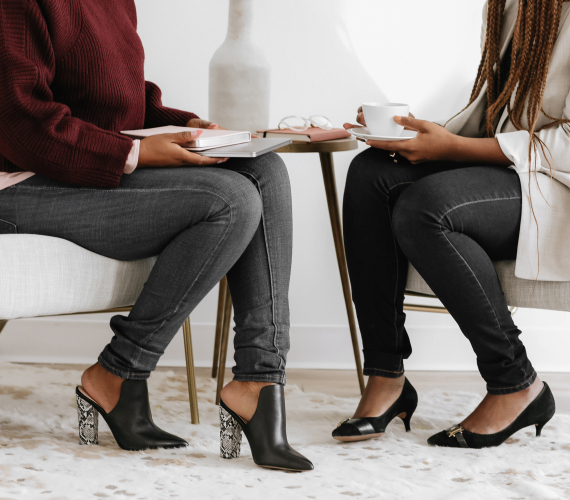 two women sitting wearing heels talking about business