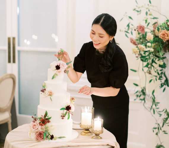 Ariel Chiu arranging florals on a white wedding cake