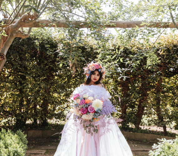 romantic maximalist bride holding bouquet beneath wooden arch