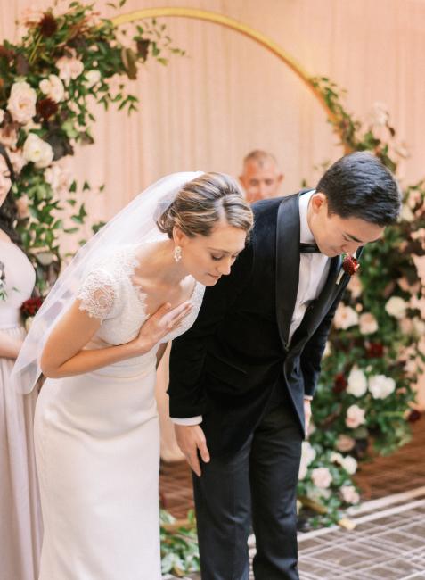 Newlyweds Bowing During Wedding Ceremony