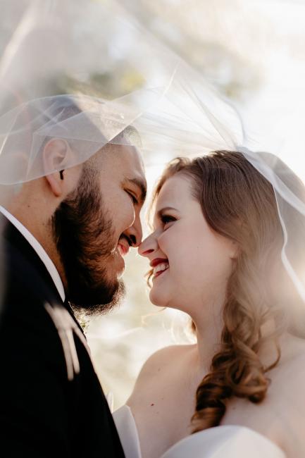 Newlyweds Under Wedding Veil