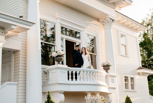 Newlyweds on Balcony of Mansion
