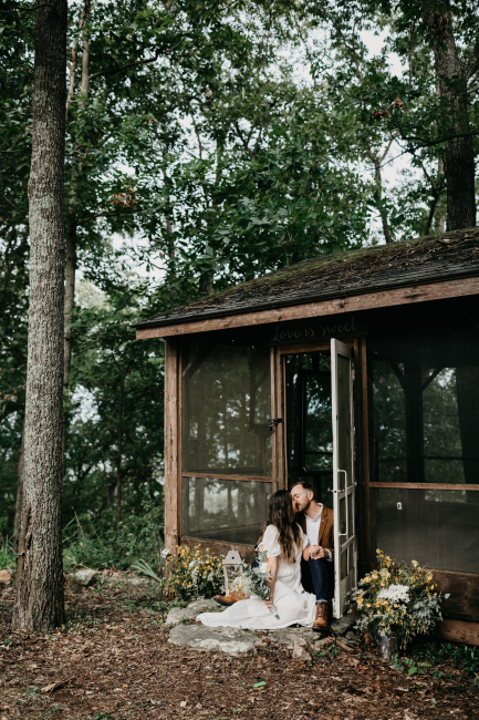 Couple Sitting in Front of Cabin
