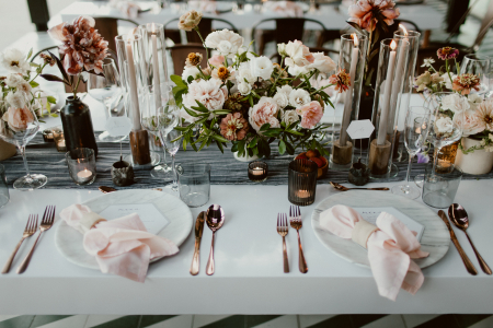 floral tablescape featuring a white tablecloth, gray table runner, marble plates, rose gold utensils and with pink and red florals