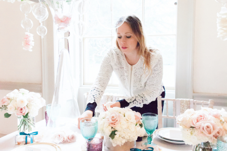 Alexandra Merri of Bijou Studio arranging florals and a place setting for an event with a creme and soft pink color scheme