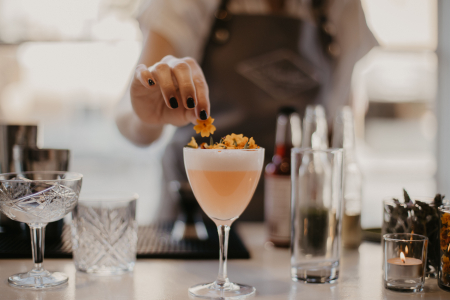 bartender adding edible flowers to a cocktail