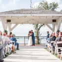 Couple at the end of the aisle getting married with their guests watching outdoors