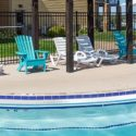 Chairs lined up on the outside of the pool for relaxing