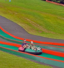 A father and daughter fly down a slope in an inner tube.