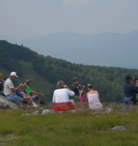 A large family surveys the valley from the top of a grassy mountain.