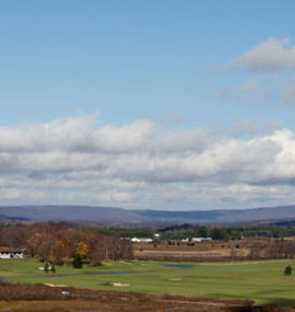 White, puffy clouds over distant mountains and the resort golf course.