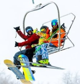Group of snowboarders and skiers on ski lift