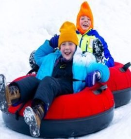 2 brothers tubing down a hill in the winter