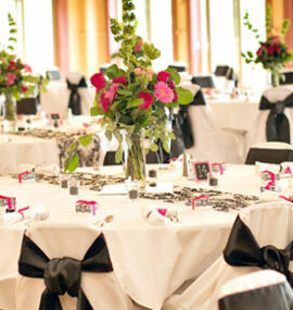 A beautiful table spread of white linens, black bows, and pink flowers.