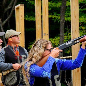 A sportswoman shoots a clay pigeon as two sportsmen watch.