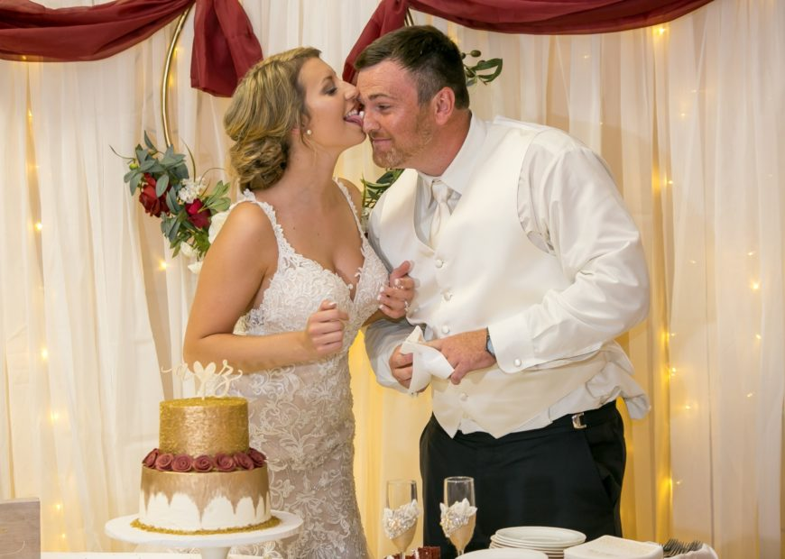 Wedding couple kissing by cake