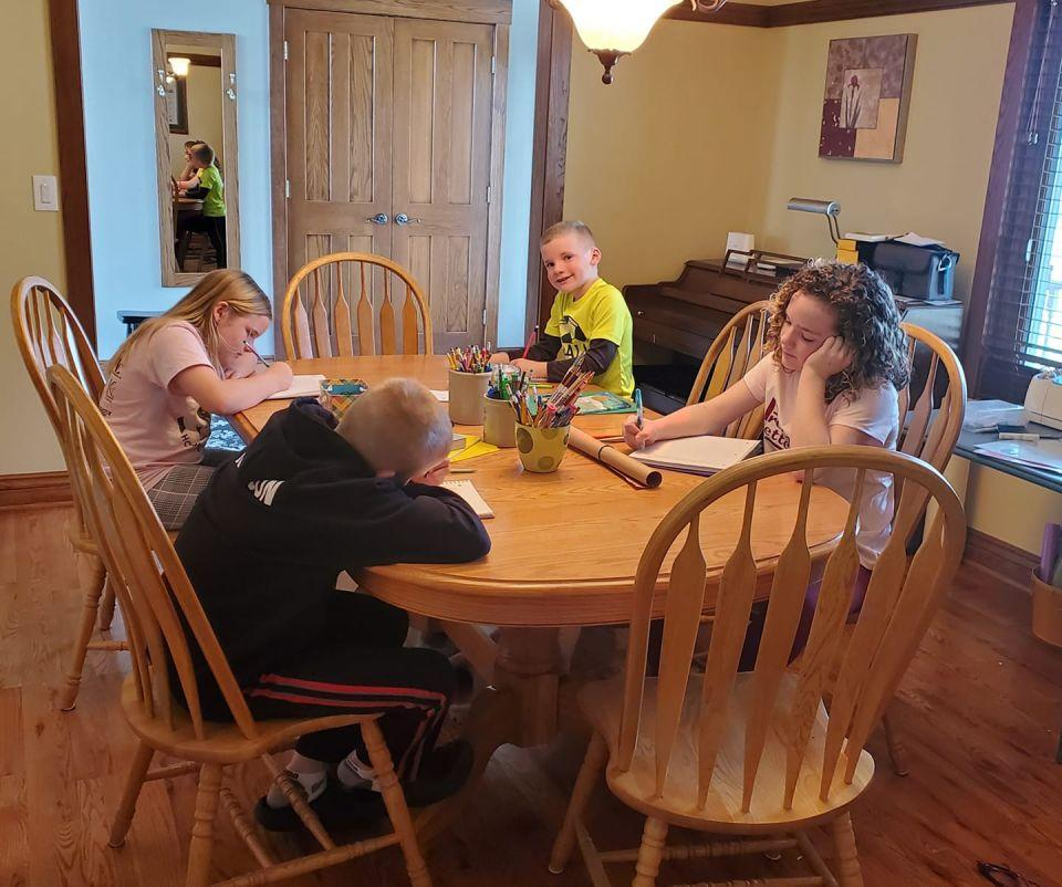 Kids at home doing projects at the dining room table.